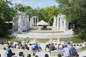 Sunny weather, people listening to a concert in the amphitheater